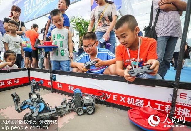8月15日,两位小朋友在宜宾学院机器人俱乐部展位免费体验机器人操控。